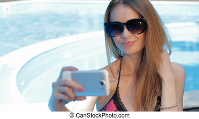 Woman makes selfie near the swimming pool