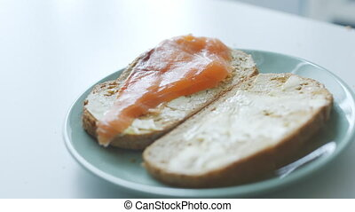 woman makes simple fish sandwiches for breakfast - womans...