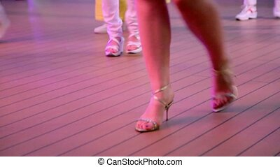 Woman makes steps during dance in latin american style