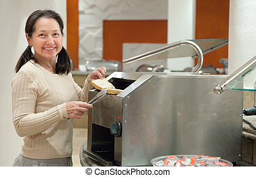 woman makes toast in toaster