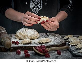 Woman makes varenyky with raspberry. Ukrainian national cuisine.