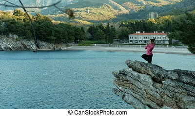 woman makes yoga exercise balance on one leg standing on rock