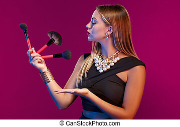 Woman makeup artist standing with brushes