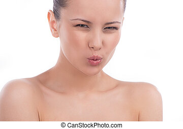 Woman making a face. Beautiful young woman grimacing and looking at camera while isolated on white