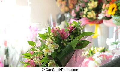 Woman making a flowers bouquet in flower shop