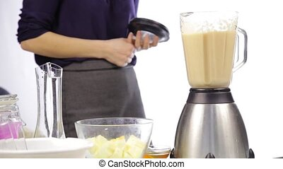 Woman making a fruit cocktail in a blender, smoothies preparation.