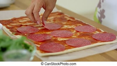 Woman making a homemade salami and mushroom pizza placing ...