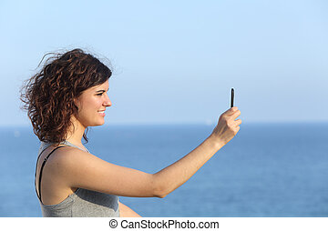 Woman making a photograph with a mobile phone