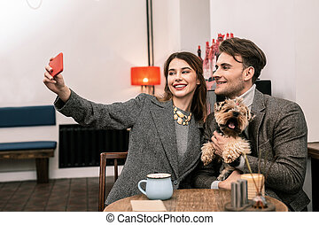 Woman making a selfie with her partner and a dog