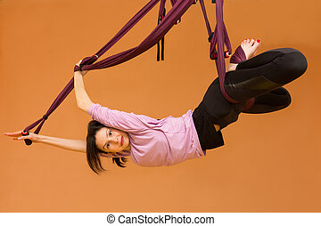 Woman making aerial yoga exercises, indoor