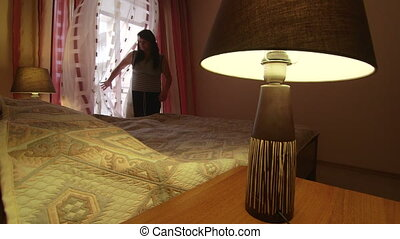 Woman making bed in bedroom dolly shot