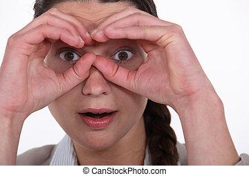 Woman making binoculars gesture with hands