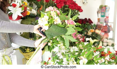 Woman making bunch of flowers in a flower shop
