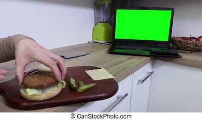 Woman making burger and watching laptop.Green screen