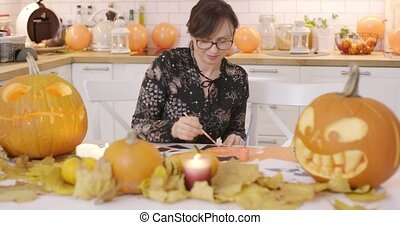 Woman making decorations - Woman in glasses sitting at...