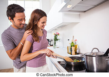 Woman making dinner with partner watching in kitchen