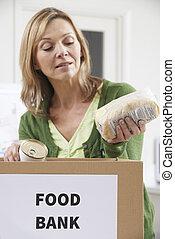 Woman Making Donation To Food Bank