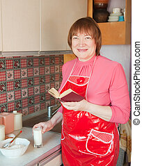 Woman making dough with cookbook