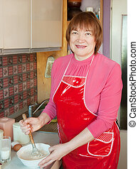 Woman making dough with whisk
