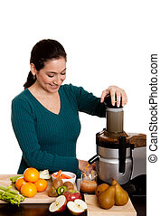 Beautiful woman in kitchen making fresh squeezed organic juice using a juicer, isolated.