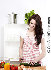 woman making funny faces while chopping cucumber for salad