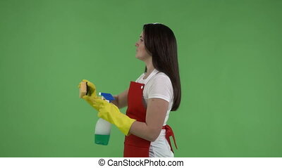 Woman making gestures as though cleans a window against green screen