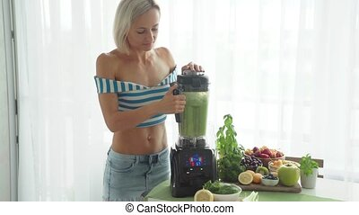 Woman making green vegetable smoothie with blender. Healthy eating lifestyle