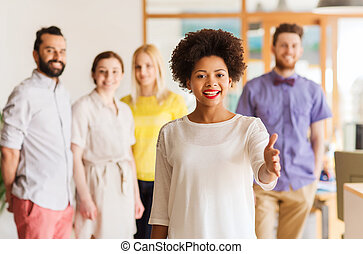 woman making handshake over creative office team - business,...