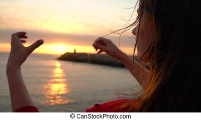 Woman making heart symbol with her hands during sunset on beach. Slow motion