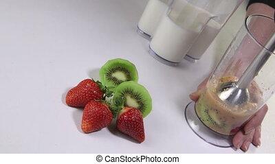 Woman making kiwi strawberry smoothie drink using stick hand blender