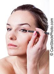 Beautiful woman making make-up using eyeliner, vertical