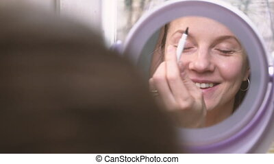 Woman making makeup and smiling looking in mirror