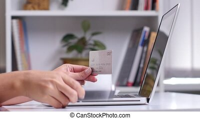 Woman making mobile payment on smartphone, woman hands holding a silver credit card and using smart phone for online shopping, girl makes a purchase online using cards and the laptop in the office, close up