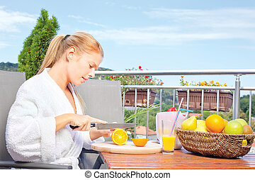 Woman making morning juice on terrace