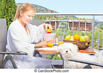 Woman making morning juice on terrace with her dog