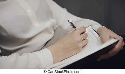 Woman making notes in notepad at home - Concentrated and...