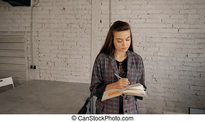 Woman making notes on paper pages about new project -...