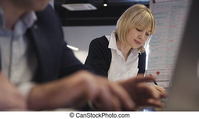 Busy and concentrated person sitting inside office working space with loft interior. Woman making presentation of new business project, smiling and thinking about hew business project