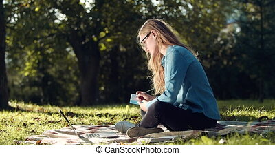 Woman making notes while studying on laptop at park - Side ...
