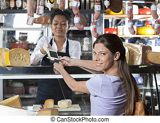 Woman Making Payment Through Credit Card At Cheese Shop