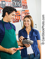 Woman Making Payment Through Mobilephone In Hardware Store