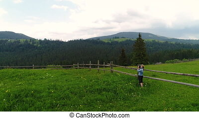 Woman making photo of summer meadow - Woman in green summer...