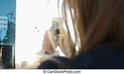 Woman making photos of the city with her phone