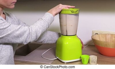 Woman making protein cocktail