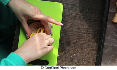 Woman making sandwiches. Using a plastic mold, it pushes a...