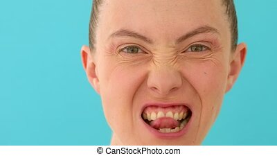 Woman making scary face to camera - Closeup young female...