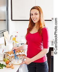 Woman making scrambled eggs with whisk