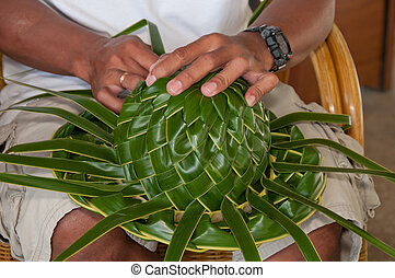 Woman making sunhat of palm leaves