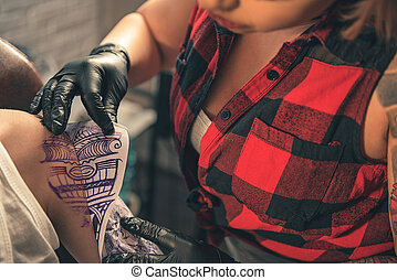 Woman making temporary tattoo on client arm