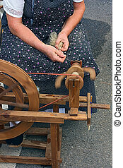 old spinning wheel - woman making thread with an old ...